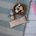 Silk eye pillow in blush silk fabric, placed on a blue and cream wool blanket