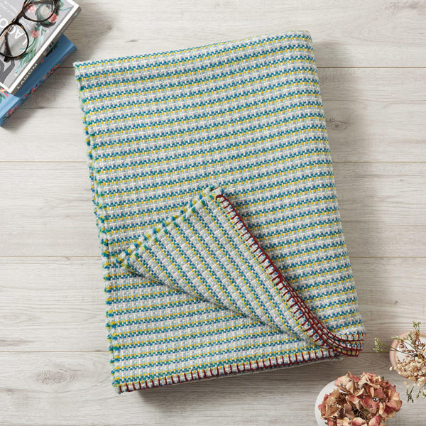 A large green, cream and yellow basketweave merino wool blanket, with red edge stitching, folded up on the floor with one corner turned up