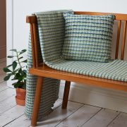 A large green, cream and yellow merino wool blanket, lain over an Ercol style bench, with matching cushion and pot plant.