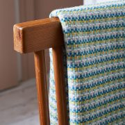 A large green, cream and yellow merino wool blanket, folded up and placed over the back of an Ercol style chair