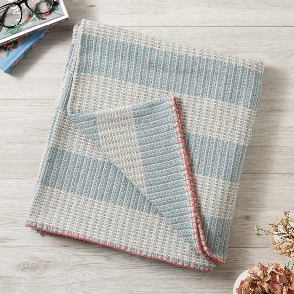 A large blue and white merino wool blanket with pink edge stitching, folded up on the floor with one corner turned up