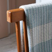 A large blue and white merino wool blanket, folded up and placed over an Ercol style chair