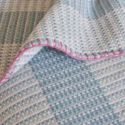 Detail shot of a large blue and white merino wool blanket, with pink edge stitching