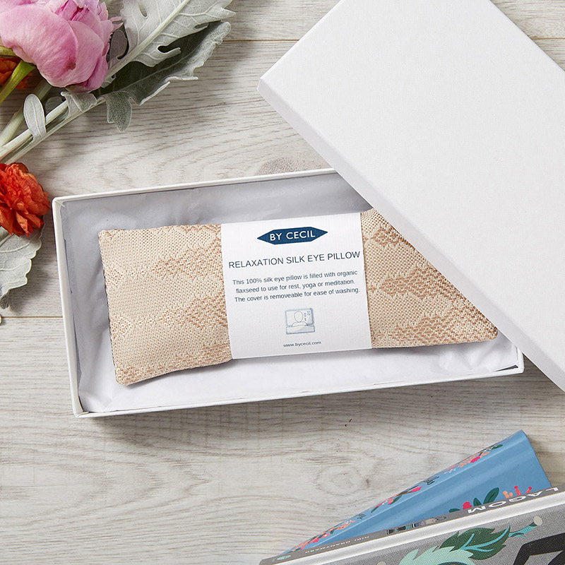 Silk eye pillow in blush silk fabric, placed inside a white box, with a white band with writing wrapped around the pillow.