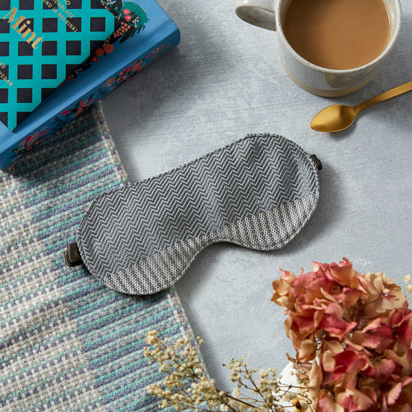 Silk sleep mask made with silver rib and twill patterned silk. Photographed from above on a blue and cream blanket surrounded by a book, dried flowers, and a cup of tea