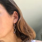 Silhouette silver earrings with black pearls on model
