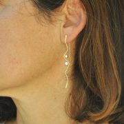 Silhouette gold earrings with pearls on model