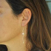 Silhouette silver pearl earrings on model