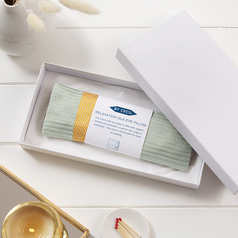 Silk eye pillow in yellow and mint silk fabric, placed inside a white box, with a white band with writing wrapped around the pillow.