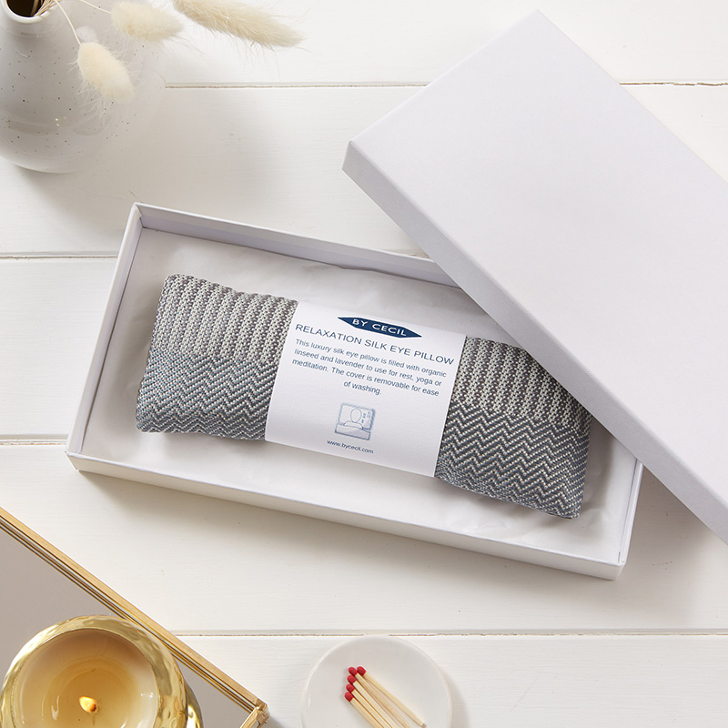 Silk eye pillow in silver silk fabric, placed inside a white box, with a white band with writing wrapped around the pillow.