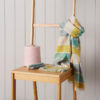 Multi coloured merino wool scarf wrapped around a brown chair. A cone of wool sits beside it.