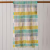 Image of a merino wool scarf hanging over a wooden pole in front of a pale grey, wooden slatted wall. The colours are turmeric yellow, jade green, pale blue and pale pink.