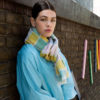 Image of a white woman with dark hair wearing a merino wool scarf. The colours are turmeric yellow, jade green, pale blue and pale pink. She is wearing an oversized blue shirt and standing in front of a wall.