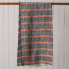 Image of a merino wool scarf hanging over a wooden pole in front of a pale grey, wooden slatted wall.. The colours are navy blue with an orange horizontal stripe