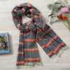 Flat lay image of a merino wool scarf. The colours are navy blue with an orange horizontal stripe