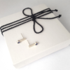 Silver stud earrings with a gemstone are placed on a white gift box tied with black cotton string.