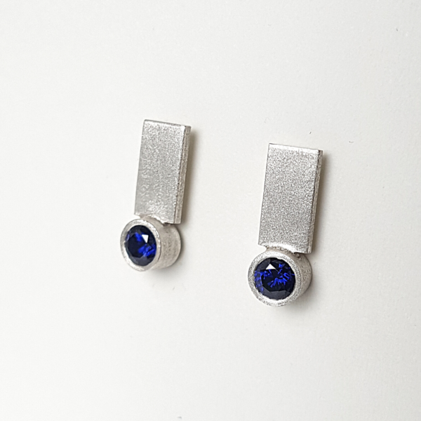 Sterling silver earrings with dark blue cubic zirconia are hanging on a white stand.