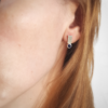 Silver sterling silver geometric stud earrings are worn on a white woman.