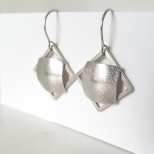 Statement silver dangle earrings hanging on the stand