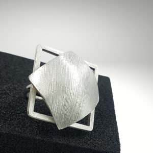 Square silver ring with a domed plate and a frame sitting on the black ring holder