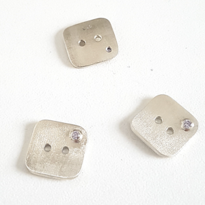 Artisan Custom Minimalist Silver CZ Apparel 3 Buttons are placed on the white surface.