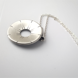Artisan oxidised sterling Silver pendant necklace is shown on a white surface.