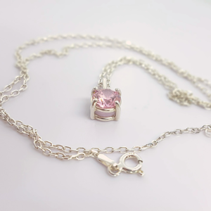 Handmade Custom 7mm Cubic Zirconia Solitaire Pendant Necklace is placed on the white surface.