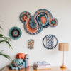 Cassandra Sabo's 'Migration' woven circular textile wall-hanging from her West Coast Collection hung on the wall above a desk with multiple circular artworks from this collection