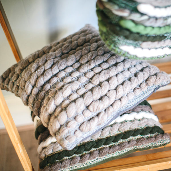 Cassandra Sabo's handwoven Merino wool square 'Burrows' cushion from her Forest Collection styled in front of the fireplace