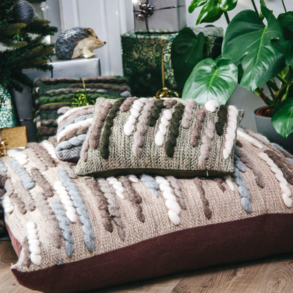 Cassandra Sabo's handwoven Merino wool rectangular 'Caterpillar' cushion from her Forest Collection styled in front of the fireplace