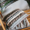 Cassandra Sabo's handwoven wool, rectangular 'Double Tendril' cushion from her Forest Collection stacked on multiple cushions