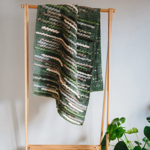 Handwoven 'Caterpillar' throw featuring Merino wool by Cassandra Sabo draped over a hanging rail