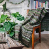 Handwoven 'Double Tendril' throw featuring Merino wool by Cassandra Sabo draped over a chair