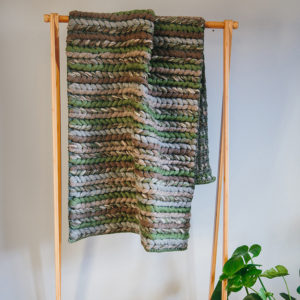 Handwoven 'Double Tendril' throw featuring Merino wool by Cassandra Sabo draped over a hanging rail