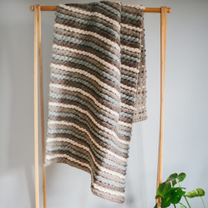 Handwoven 'Tendril' throw featuring Merino wool by Cassandra Sabo draped over a hanging rail