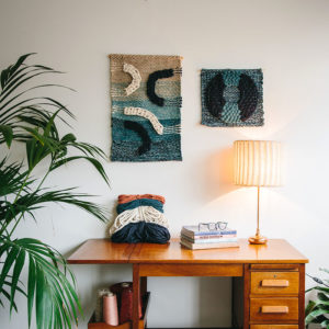 Cassandra Sabo's 'Flow' handwoven textile wall-hanging from her West Coast Collection hung on the wall beside the 'Salmon' wall-hanging.