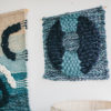 Cassandra Sabo's 'Flow' handwoven textile wall-hanging from her West Coast Collection hung on the wall beside another 'Macraweave' wall-hanging.
