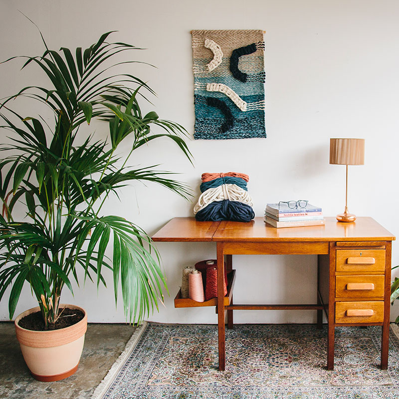 Cassandra Sabo's 'Salmon' handwoven textile wall-hanging from her West Coast Collection hung on the wall above a desk