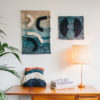 Cassandra Sabo's 'Salmon' handwoven textile wall-hanging from her West Coast Collection hung on the wall beside another Macraweave wall-hanging.