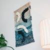 Cassandra Sabo's 'Salmon' handwoven textile wall-hanging from her West Coast Collection hung on the wall and photographed at an angle.