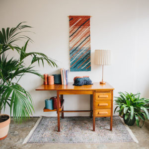 Cassandra Sabo's 'Shoreline' handwoven textile wall-hanging from her West Coast Collection hung on the wall above a desk