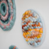 Cassandra Sabo's 'West Coast 2' woven circular textile wall-hanging from her West Coast Collection hung on the wall with multiple artworks from this collection