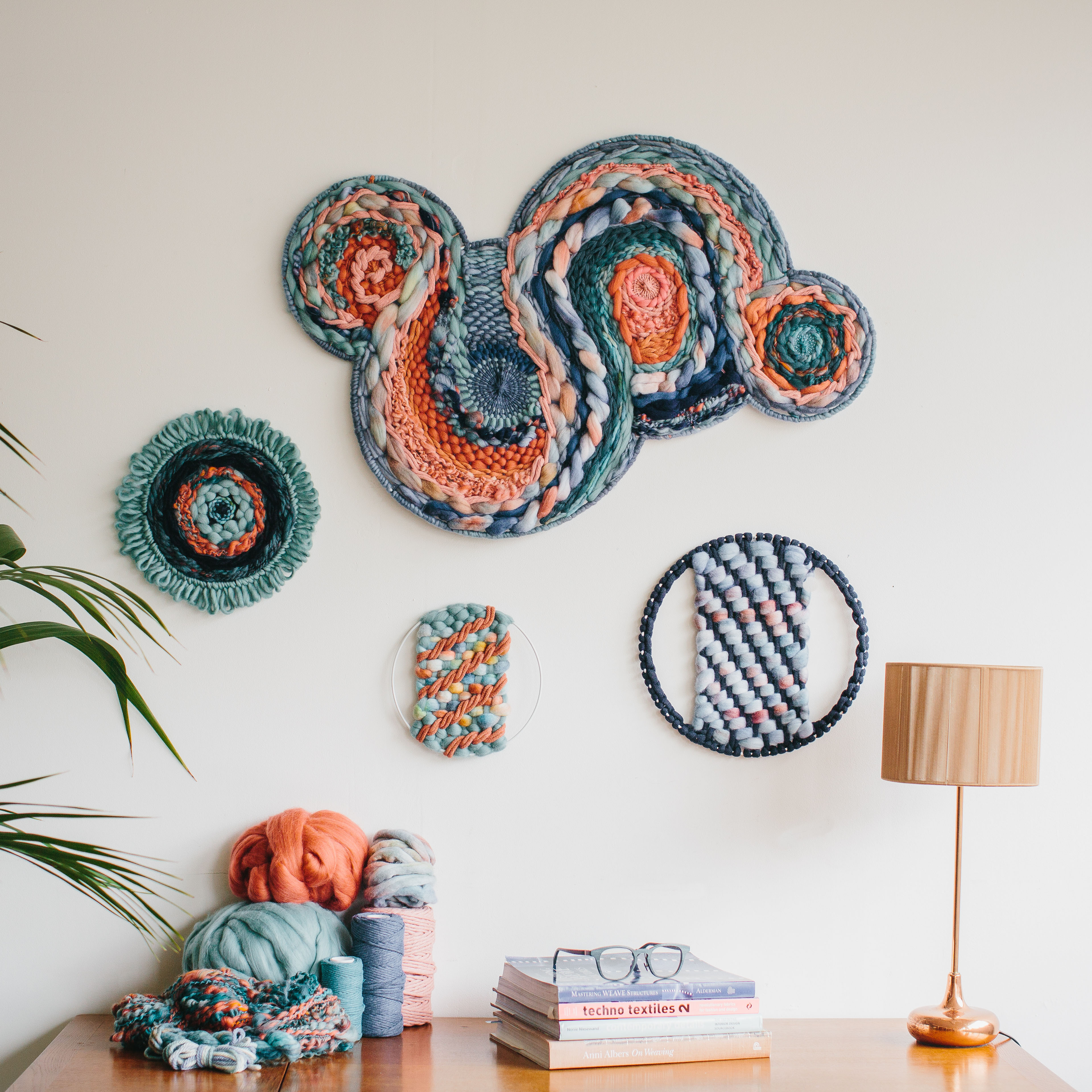 Cassandra Sabo's 'West Coast 8' woven circular textile wall-hanging from her West Coast Collection hung on the wall with multiple artworks
