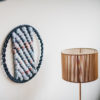 Cassandra Sabo's 'West Coast 8' woven circular textile wall-hanging from her West Coast Collection hung on the wall beside a table lamp