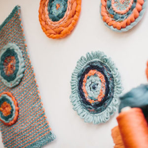 Cassandra Sabo's 'West Coast 1' woven circular textile wall-hanging from her West Coast Collection hung on the wall with multiple artworks from this collection