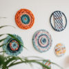 Cassandra Sabo's 'West Coast 9' woven circular textile wall-hanging from her West Coast Collection hung on the wall with multiple artworks