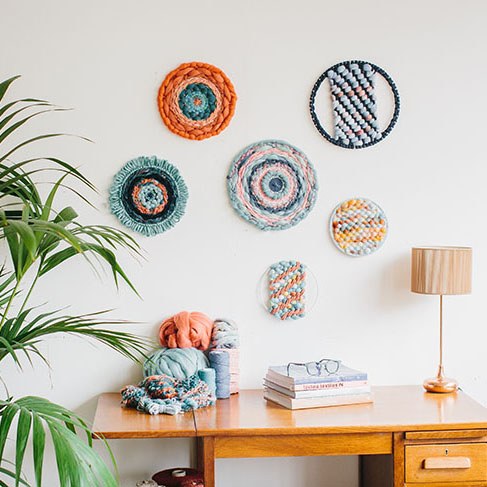 Cassandra Sabo's 'West Coast 2' woven circular textile wall-hanging from her West Coast Collection hung on the wall above a desk