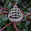 Silver Beaded Quatrefoil Ring - view from the back - against foliage background