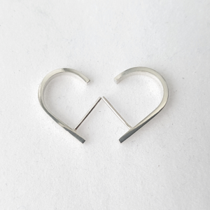 Minimalist J-shaped silver earrings are placed on the white surface.