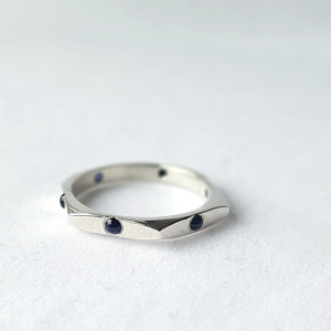 Sterling silver ring with six Cabochon Sapphires is placed on the white surface.